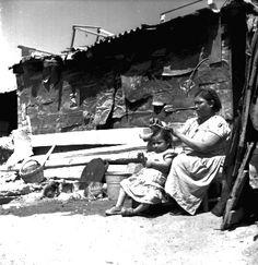 02-1951 Mujer peina a una niña en la puerta de su vivienda
