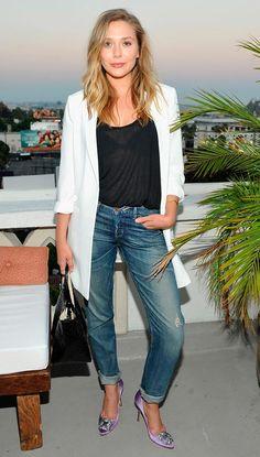 Street style look com blazer branca, blusa preta e calça jeans.