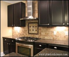 dark cabinets, white subway tile backsplash, and revere pewter