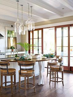 In this open and bright kitchen, sliding glass-paned doors let in light while connecting the kitchen to the porch. Dark wood tones add dimension to the light, white space. A half-circle table attached to the island doubles as New Kitchen, Kitchen Dining, Kitchen Decor, Bright Kitchens, Home Kitchens, Dream Kitchens, Neutral Kitchen, Kitchen Photos, Deco Design