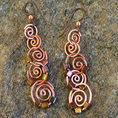 I would connect them with top lopes. Copper Spiral Earring w/ Bronze Iris Glass Cubes by funkypretty, $28.00