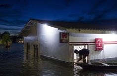 A resident leaves a Bradesco bank in a street flooded by the rising Rio Solimoes, one of the two main branches of the Amazon River, in Anama, Amazonas state, Brazil May 28, 2015. According to the state Civil Defense, more than 237,615 people were affected in the State with strong rains. Picture taken on May 28, 2015. REUTERS/Bruno Kelly
