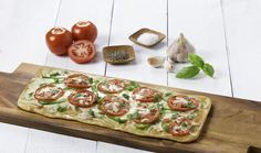 Flatbread on a cutting board with peppers, tomatoes, garlic, shredded cheese, basil and salt and pepper. Yes, it's that easy! #FreshFromFlorida