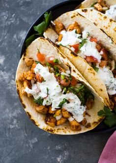 Quick 20 minute grilled chicken tacos topped with pico de gallo and creamy cilantro sauce. These spicy tacos are perfect for weeknight dinners and are sure to please the entire family. | Gimme Delicious