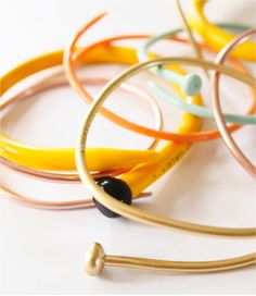 How to make knitting needle bracelets Boil plastic needles 20 min; heat metal ones 140degrees 20 min. Use heatproof gloves to form around drinking glass. Remove and clip to hold shape.  Cool.