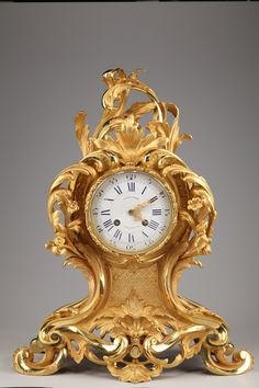 An+exquisit+small+gilt+and+chiseled+wall+clock+in+Louis+XV+style+resting+on+a+base+with+four+foliated+feet,+profoundly+sculptured+with+asymmetric+acanthus+leaves,+openwork+rocaille,+scrolls