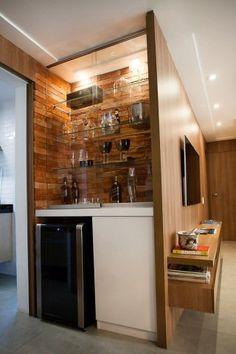 """Tijolos aparentes ao fundo contrastam com a laca branca e as portas em vidro no bar/adega deste apartamento em São Paulo (SP). """"A adega se destaca na decoração e ao mesmo tempo está integrada dentro do nicho atrás do painel da televisão"""", explica a arquiteta Carolina de Nani, que assina o projeto. A capacidade de armazenamento total do espaço é de 36 garrafas, em média."""