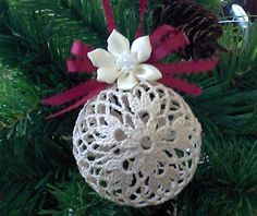 "Crochet Ornament : flower pattern on both sides, with the rest of ornament in a mesh pattern. Burgundy color ribbon bow and hanger, with Ivory color flower hot glued to the top. Stiffened with ""Stiffy"" fabric stiffner. Measures approximately 3"" high, by 3"" wide, 8 1/2"" circumference"