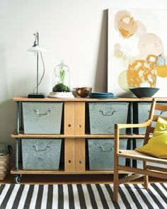Going for the industrial look? You'd be surprised at how well metal accents wood. Slide metal bins into wooden shelves to hide and store anything guests don't need to see. | marthastewart.com