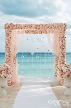 pink and white arbor covered in flowers drips with crystal strands and glass bubbles filled with flower petals