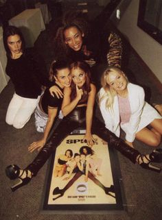 The Spice Girls pose with one of their (many) posters that adorned the walls of 90s boys and girls.