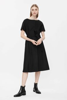 This dress is made from a wool-mix with a soft finish and a detachable stitched belt. A close fit, comes in at the waist and flares towards the hemline, it has hidden front buttons, a box pleat at the back and subtle in-seam pockets.