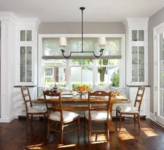 game table and chairs with chandelier between built-ins