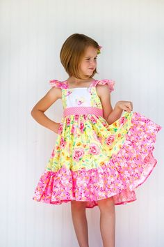 The Sophia dress is a handmade vintage style girls summer dress in bright pink and yellow floral cotton fabrics. This vintage style pattern includes a sash around the waist that ties in the back, flut