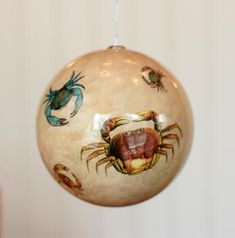 Sea Creature Ball Ornament, by Seasons of Cannon Falls. Softly colored ball ornament decoupaged on the inside with red and blue crab images. Made of paper/foam inside acrylic ball. Measures 4 inches in diameter.