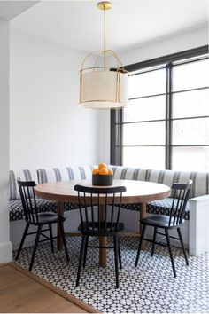 dining room 156007574578698384 - A white drum cage pendant hangs over an oval wood dining table placed on white and black mosaic floor tiles and seating two black Windsor dining chairs facing a white l-shaped dining banquette. Source by knatschinats Room Tiles Design, Dining Room Design, Dining Decor, New Kitchen, Kitchen Decor, Kitchen Design, Awesome Kitchen, Kitchen Modern, Windsor Dining Chairs