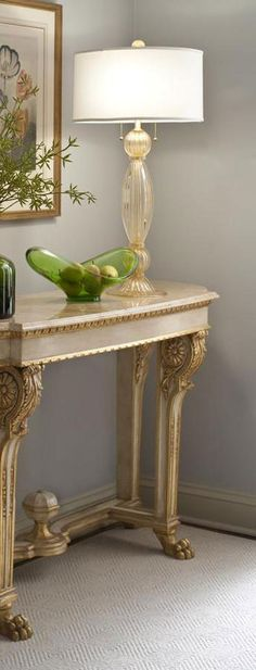 room setting with clear and gold Venetian glass lamp hand blown on the island of Murano (Italy) and Empire style carved wood console table with marble top