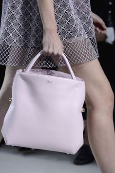 Time for some new arm candy, Dior 's curvaceous new tote is pretty in palest pink.