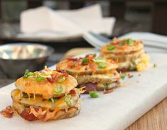 stacked potato slices with melted cheese, scallion and bacon