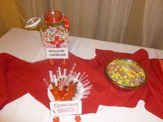 Jeringas con jugo de naranja y granadina. Caramelos variados en un frasco con un lazo rojo. Un bowl con golosinas.