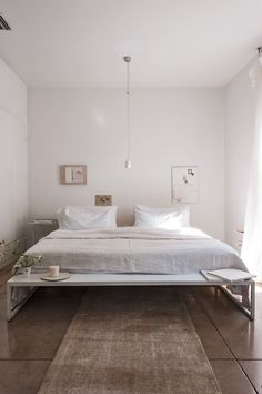 Bedroom Art Tip: Designer Michaela Scherrer's bed feels spacious even though the bed takes up most to the room. That's because both her bed and the art on the walls are positioned toward the lower half of the room, leaving the upper half virtually empty.