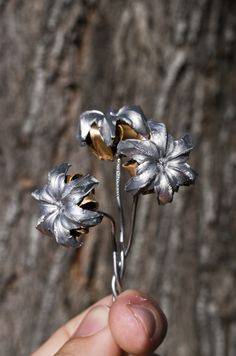 """""""Flowers"""" made by shooting a 1911 gun (don't ask me what kind of gun that means!) underwater & soldering them onto stems."""
