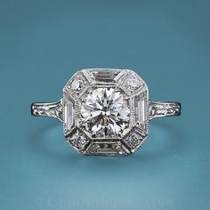 A very fine European cut diamond is embraced by both baguette and round cut diamonds in this Art Deco diamond engagement ring. The 1.01 carat diamond, accompanied by a GIA certificate stating H color, VS2 clarity, is set within an octagonal setting which is brightened with alternating trapezoid and round cut diamonds with a beautifully engraved shank. An original Deco delight!