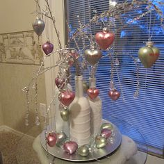 This is the same centerpiece made at Christmas using repurposed wine bottles. Post-Christmas bulbs are replaced with Valentine ornaments purchased from Lillan Vernon catalog.