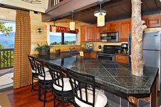 A Gatlinburg Cabin Kitchen With Granite Countertops, Wooden Cabinets, And  Stunning Views Of The Smoky Mountains