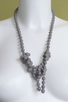 dip necklace, short knotted chain with plastic skin. every necklace is unique.    the chainsareentangledand at different placesfused togetherby theplastic skin, creating anew abstractshape.