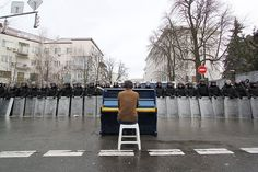 Kiev: Man playing piano to riot police