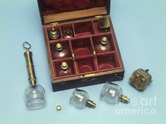 Cupping set in a wooden case with a red lining. The set comprises of six glass cups, two scarificators, a spirit burner, a syringe and a tincture bottle. This set would have been used in a procedure called 'wet cupping', a form of bloodletting used in the nineteenth century to 'treat' a range of ailments. This set was made in England and dates from the year 1850.
