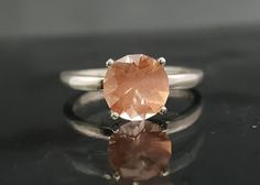 This+one+a+kind+Oregon+Sunstone+was+personally+cut+by+me.+The+weight+is+1.14+carats+and+is+approximately+7.05+mm.+The+stone+has+a+beautiful+color+with+schiller+(peach+color)+from+the+copper+inclusions+only+found+in+Oregon+Sunstone.+It+is+mounted+in+a+size+5+sterling+silver+(925)+ring.+This+could+...