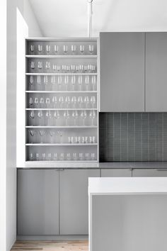 Modern kitchen by Anne Sophie Goneau Design. Loving the glass storage-the glasses almost disappear within the grey cabinetry.