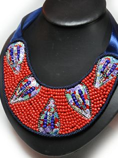 Collar babero realizado con rocalla en azul y rojo y latón con motivo floral. Cierre de lazada. http://www.chanchelcomplementos.com/en/shopping/categoria-collares/collar-babero-rocalla-detail.html