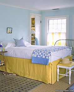 A butter-and-cream yellow bed skirt works best when warmed by an orange-yellow curtain stripe, and chilled, a bit, by breathy aqua walls. The overall effect is clean and simple, with a sunny touch.