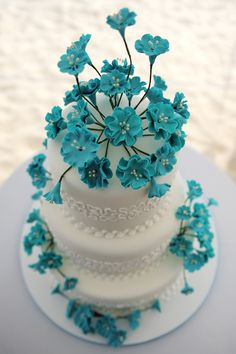 Very cool turquoise flowers on this white cake.