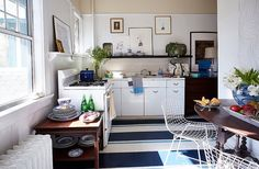 """The kitchen's linoleum floor received a bold makeover. """"Painting a floor isa way to add color, pattern, and interest in a space that normally doesn't have patterns or upholstery in it,"""" William says. Hekept the shelving open so that he could display his china and other collections."""