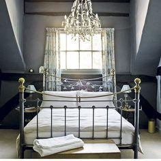 Grey bedroom with metal bedstead and chandelier