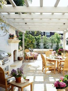 Love this outdoor space with its fireplace, outdoor kitchen, white pergola and light wood furniture.
