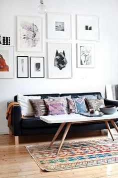 Black leather couch with white and wooden coffee table, wall art, Colourful pillows and rug