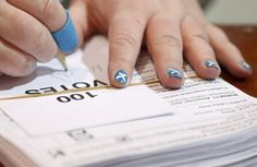An electoral worker with a Scottish Saltire painted on her finger nails counts ballots after polls closed in Britain's general election at a counting centre in Aberdeen, Scotland | El mundo en un golpe de vista - Yahoo Noticias