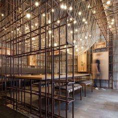 Shanghai-based Lukstudio has reinterpreted a traditional Chinese food drying rack with a metal grid structure and hanging wires for a noodle bar in Changsha