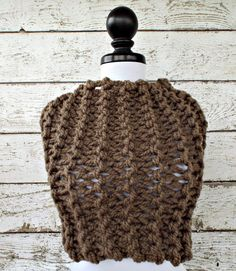 This cozy soft cowl is lofty, yet warm. Perfect to dress up a plain t-shirt or wear with your favorite jacket, this cowl is a great piece for colder and transitional months. This cowl is knit in a neutral taupe brown coloured wool blend yarn. This oversized cowl measures 27 inches around