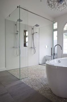 Clean white bathroom using white pebble tile floor in shower and as flooring.