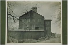 """1890 Scitico, CT   JD Stowe   Industrial masonry brick factory building with flat-topped center cupola and three-story projecting addition on right. Tall ladder is against building on right next to barrels, lumber and bricks. In front is one story board and batten building with ventilating shaft on roof. At right is dirt road with stone wall and rail on left. Inscription on back: """"Paper Mill at Scitico (Enfield) #1"""""""