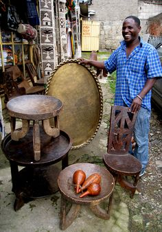 Ethiopian trader with selection of stools for sale.   Taken on one our many buying trips to Ethiopia.