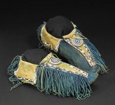 A pair of Southern Plains beaded moccasins. Kiowa or Comanche, the entire instep and fringe dyed a rich blue, a tapered band with green pigment and lane beading down the vamp, the keyhole-form tongue with beaded roundel, edge beading on the ankle flaps and more fringe trailing at back. length 11 1/4in   (RVYWQ - B-6/10))