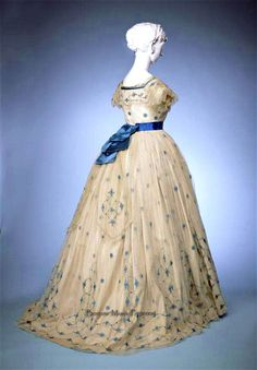 Evening gown, 1865. Bodice & skirth of white gauze embroidered with flowers in bright blue silk and trimmed with Lisle machine lace. Blue silk ribbon sash. Gemeentemuseum Den Haag via ModeMuze