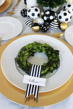 Black, gold and white holiday decor! We used boxwood topiaries, DIY black & white polka dot ornaments and Sugar Paper's gift topper set fromTarget to create  this year's Christmas decorations for our table. For each place setting we used mini boxwood wreath, black & white striped ribbon and a simple place card. by jane can...